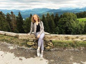 Mulher sentada numa cerca bsixa de madeira e com mobtanhas e árvores coníferas ao fundo.